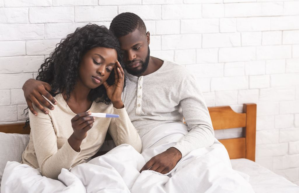 Couple sitting on bed with negative pregnancy test results