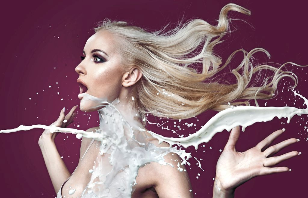 Beautiful blonde woman being splashed with white liquid