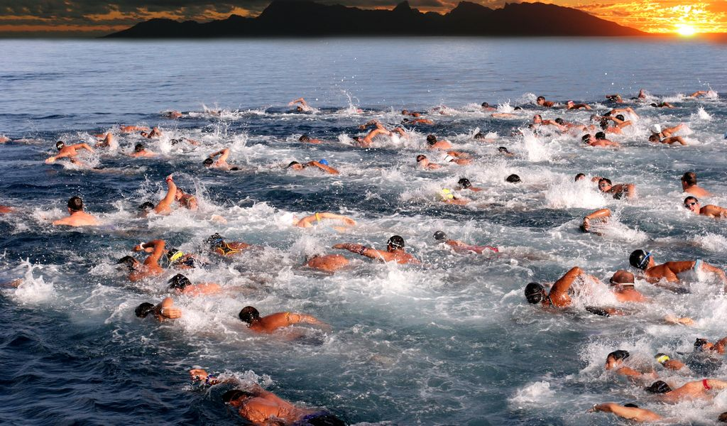large number of men swimming in the ocean mimicking sperm motility